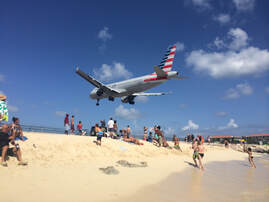 Tourists on beach watching jet landing